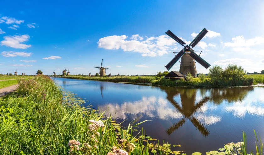 Windmills and water canal in Kinderdijk in a beautiful summer day, Holland