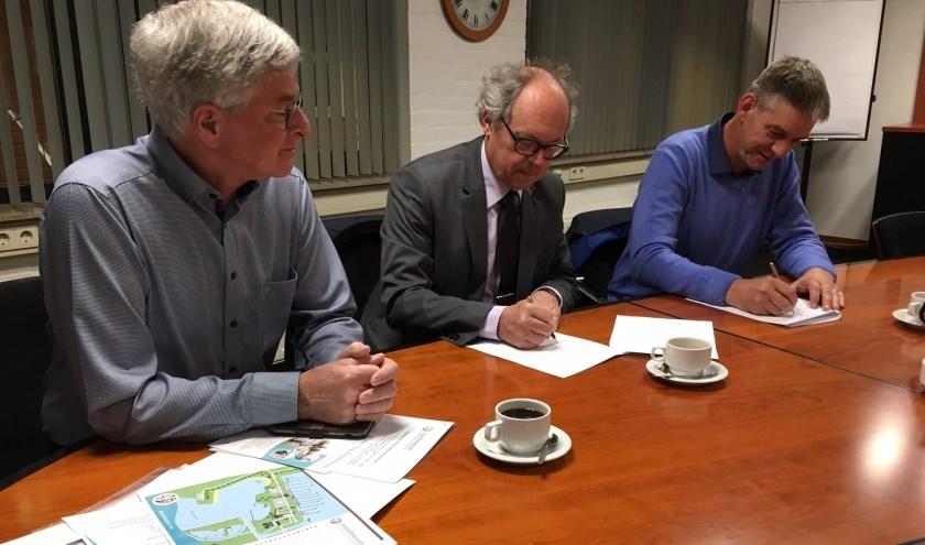 • Jos van Gent (rechts) en wethouder Jan-Hein de Vreede ondertekenen de afspraken over het toezicht, onder toeziend oog van Kees de Jong.