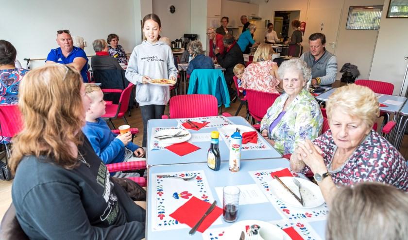• De buurtbewoners aan de gezellige gedekte tafels.