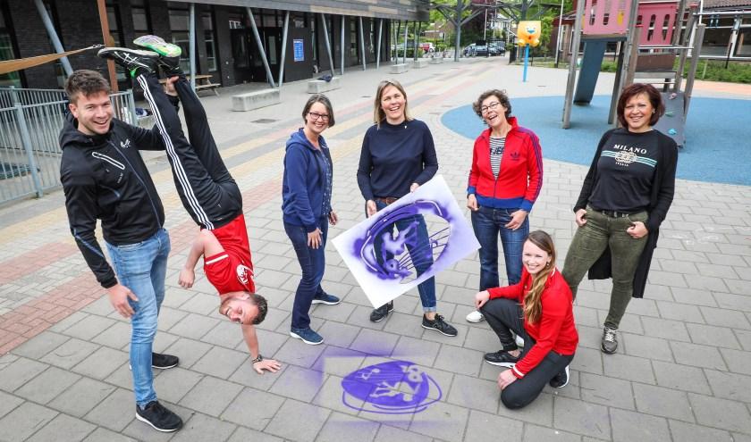 • Teamleden van Welzijn Bommelerwaard en Spel&. Eugenie Kaspori houdt de mal met het nieuwe logo vast.