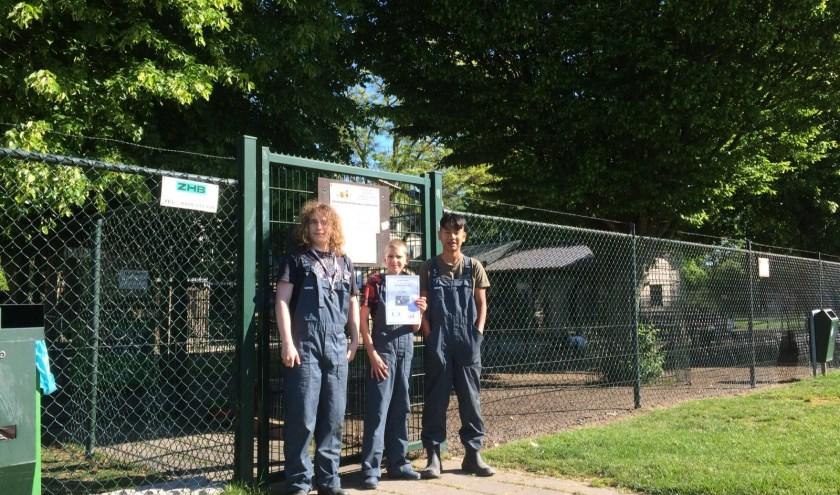 • Drie leerlingen van De Brug staan bij de kinderboerderij met het bewijs van adoptie van de dwerggeiten.
