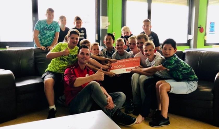 • Wouter Rijneveld met enkele jongeren en de cheque.
