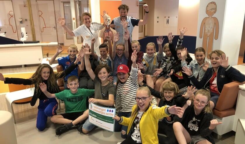 Alle kinderen van groep 7 CBS Het Kompas Vuren met dokter Natasja Dors en meester Daan op de achtergrond