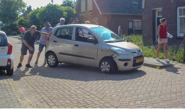 • Omstanders zetten de auto weer op vier wielen. Foto: Mark Verlijsdonk / Versteeg AV Producties © Bommelerwaard