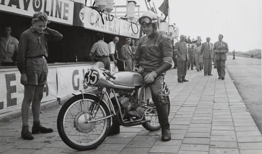 • Jan Muijlwijk op zijn zelfgebouwde motorfiets tijdens de TT races in 1954. Koen is het het jongetje in korte broek.
