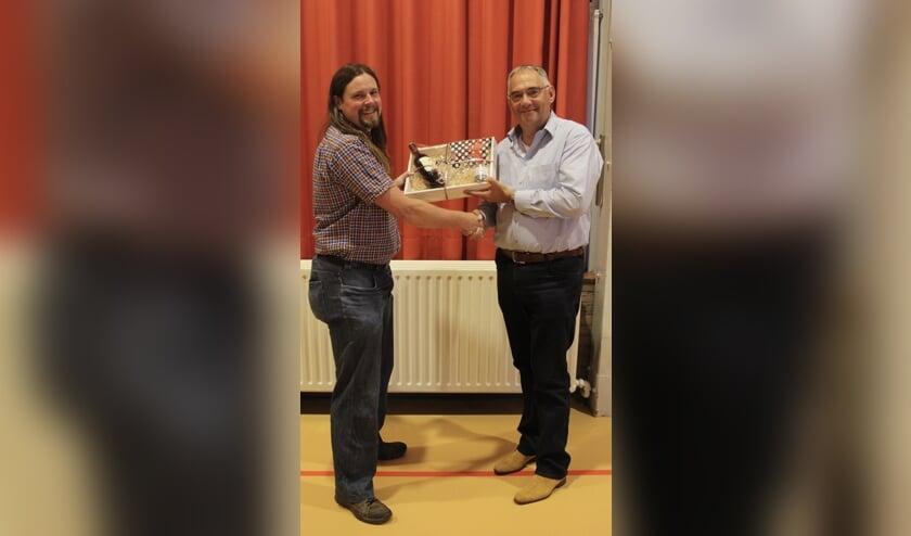• Voorzitter Dennis van As (links) overhandigt Jan van de Sanden een afscheidscadeau.