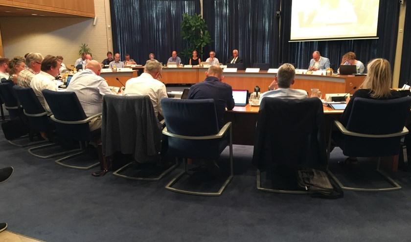 • Wethouder De Vries, eerste links naast het scherm, tijdens de vergadering waarin de VVD met een motie van wantrouwen kwam.
