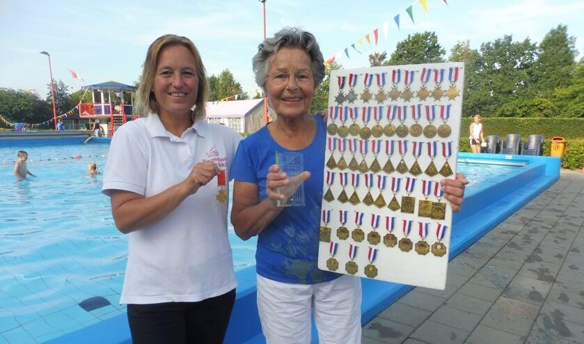 Ria van Bennekom krijgt haar 50e medaille èn oorkonde van de zwembond voor haar 50e zwemvierdaagse uitgereikt door Elmy van Maastrigt