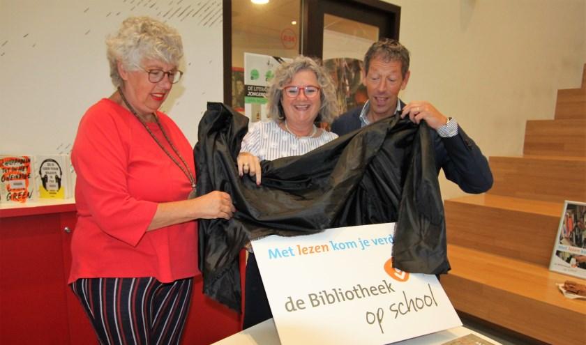 • Conny Reijngoudt, Kirsten Jaarsma en Ad Keller onthullen het logo van de bibliotheek in de school.