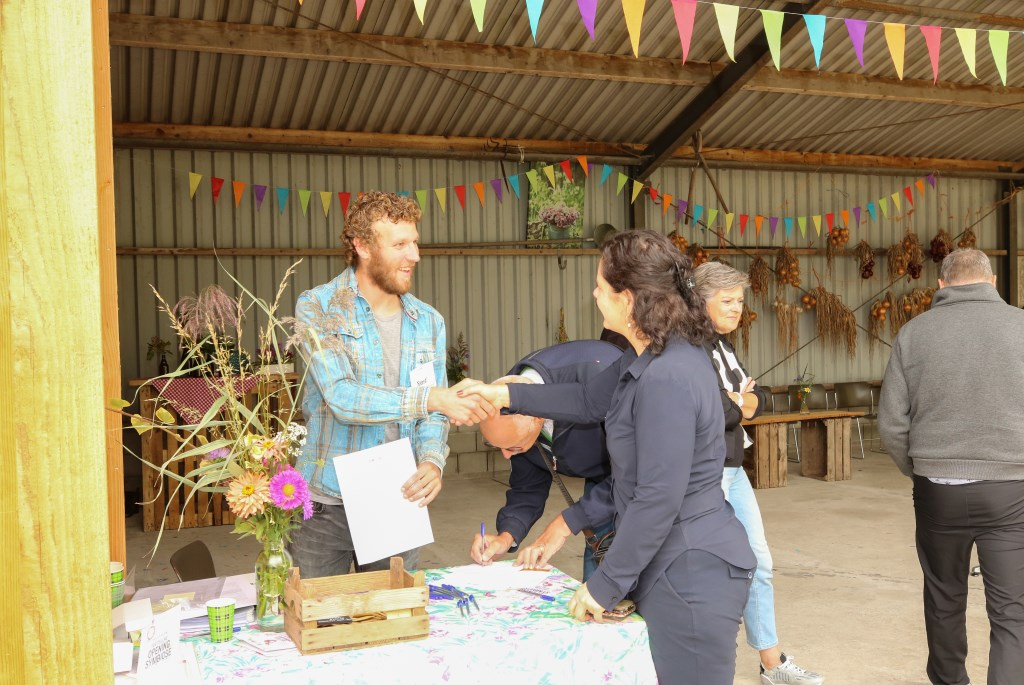 • Biologisch-dynamische boer René Bor (links) overhandigt een envelop met pas aan een klant. Foto: Aangeleverd © Alblasserwaard