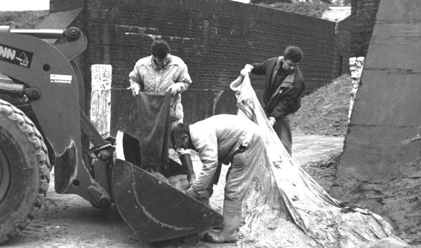 Drie personen maken in Woudrichem zandzakken leeg na een periode van hoogwater.