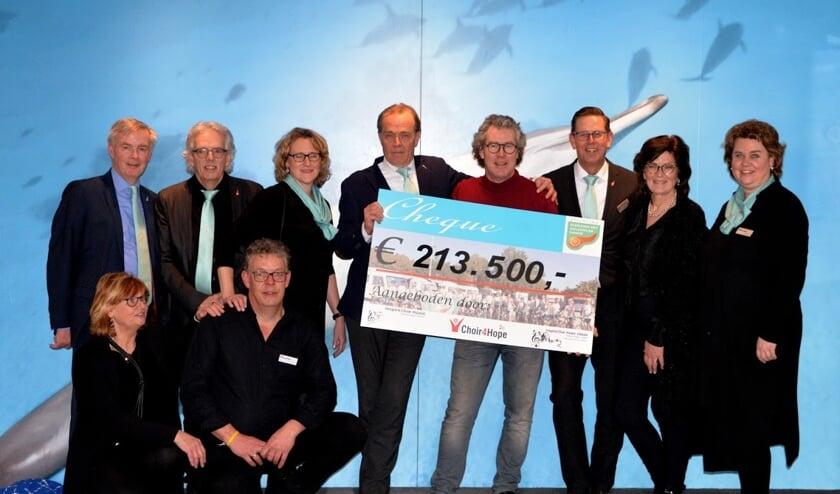 • prof.dr. Casper van Eijck (met de cheque in handen) met naast hem Peter Overduin (in rode trui) en enkele bestuursleden van beide koren.