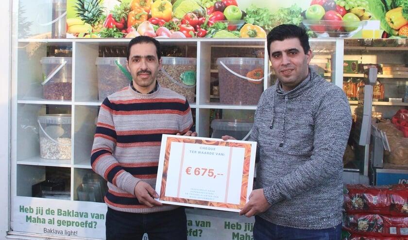 • Rateb (rechts) overhandigt de cheque aan Mohammed.