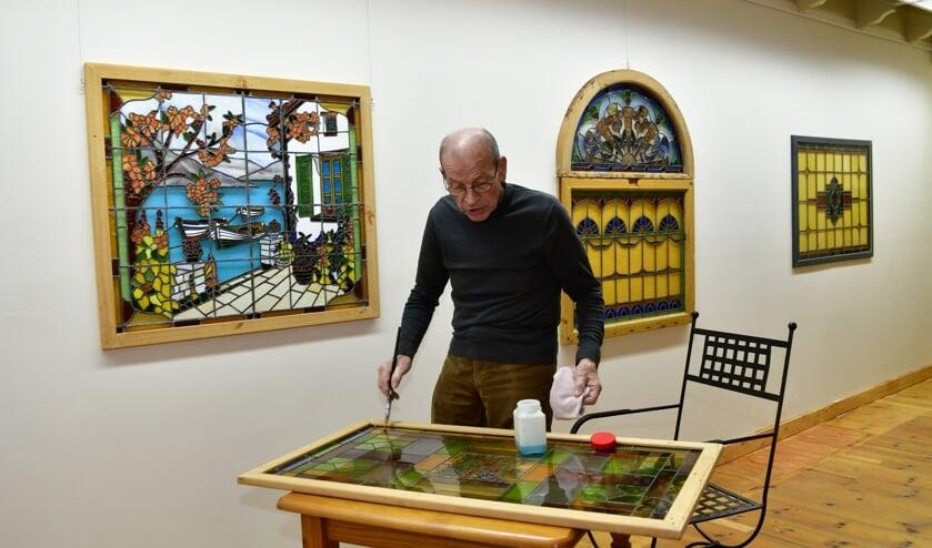 • Gerrit van IJzeren in de nieuwe galerie, bezig met één van zijn panelen.