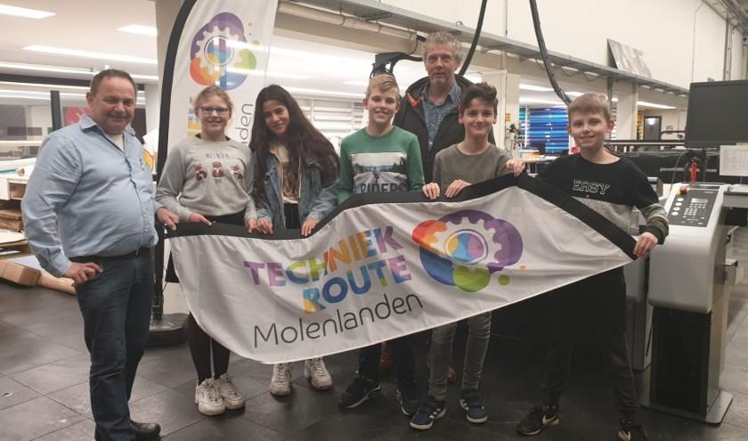 • Wim van Heteren en enkele leerlingen overhandigen de vlag aan Adri Korteland.