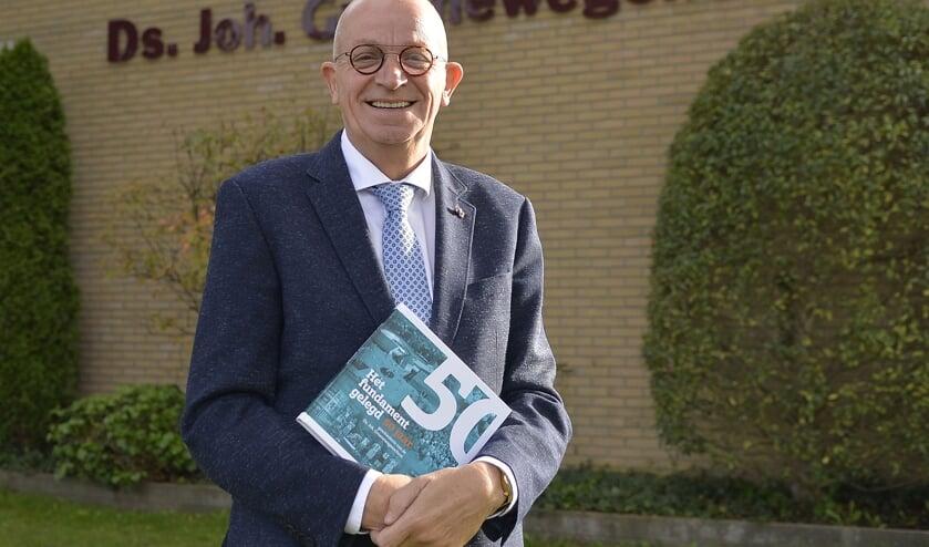 <p>Schooldirecteur Ad Geuze met het jubileumboek.</p>