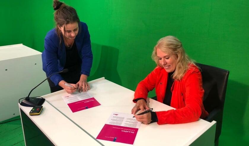 Lizanne Lanser (r) en Marlous Fieret ondertekenen het actieprogramma