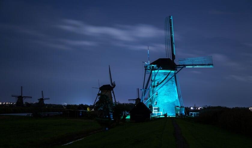 • Een blauw verlichte molen in Kinderdijk.
