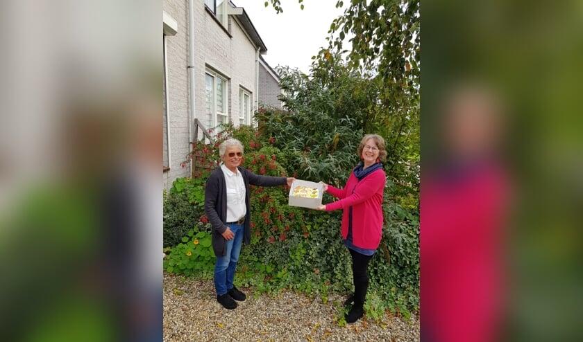 • Ineke van Wijnen (links) overhandigt de taart aan Yvonne Stam.