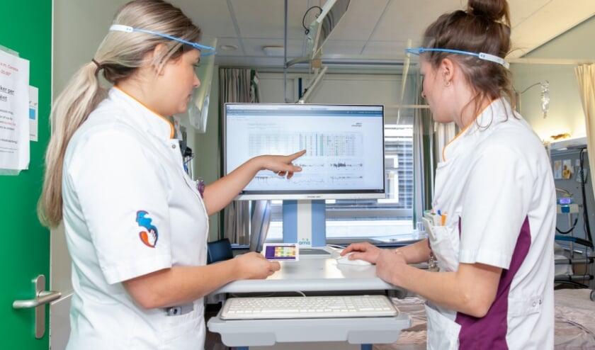 • Arts-assistent Shelly van Nieuwkasteele (links) en verpleegkundige Carla Groenendijk bekijken de risicoprofielen van alle op dat moment opgenomen patiënten op de afdeling.