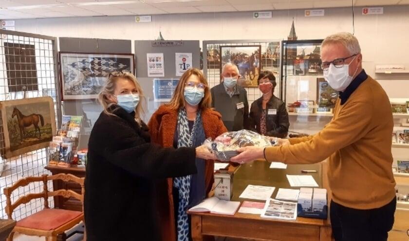 <p>Lex van Wijk (r), voorzitter van Stadsmuseum De Knoperij begroet de 1000e bezoeker en verrast haar met een Montfoort pakket. Foto: Peter Versloot&nbsp;</p>