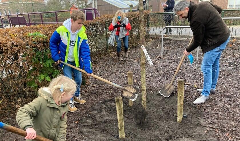 <p>&bull; Pien en Jorey helpen de wethouder bij het planten van de boom.</p>
