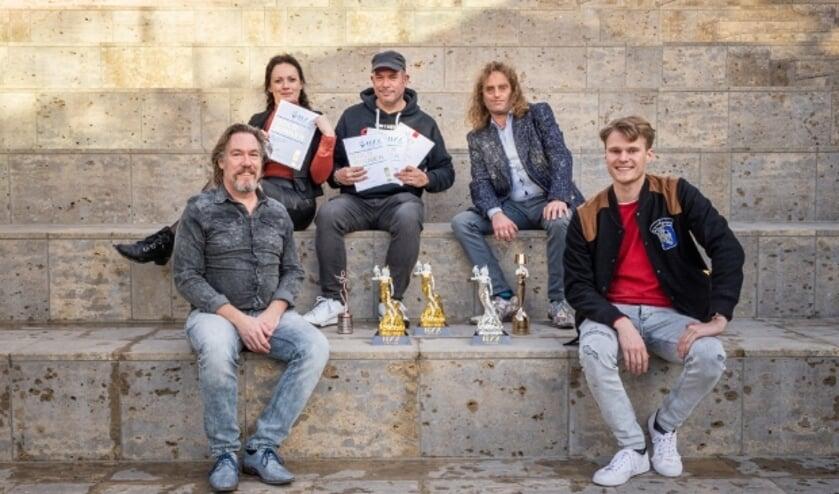 <p>De jonge Montfoortse ondernemer Chiel Baauw (rechts) van The New Standard met zijn partners van ontwerpbureau IDEA 2 en Draeckensteijn Media. Met in het midden: de awards. (Foto: PR)</p>