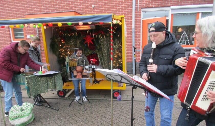 • Marian Verdonk op accordeon (r) begeleidt cliënten van de Lingebolder bij de muziekkar in Kerstsfeer.