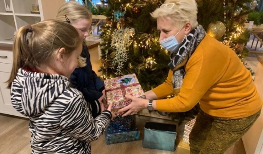 <p>Maaike en Iz&eacute; bieden de doos met zelfgemaakte kerstkaarten aan. Foto: Tineke Giesbers</p>