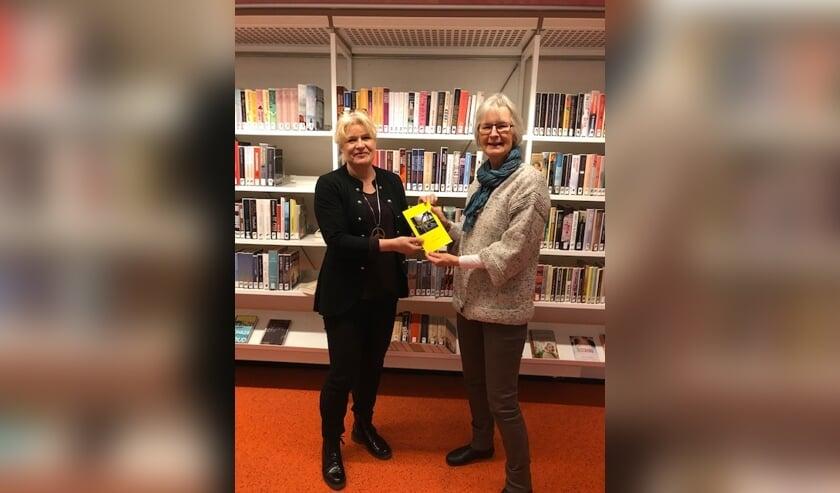 • Bep van Veenendaal (rechts) overhandigt haar boekje aan Thea de Jong.