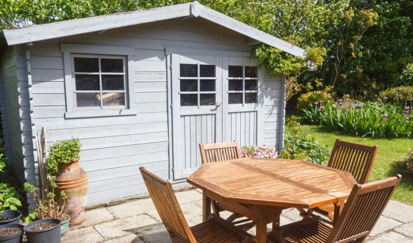 Shed with terrace and garden furniture in a garden during spring