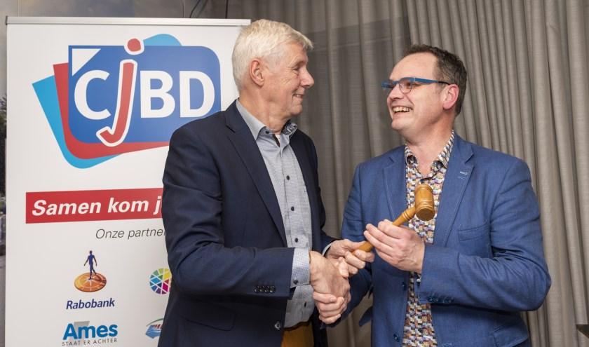 • Harry Eskes (links) draagt met de voorzittershamer zijn taken over aan Johan den Houter.