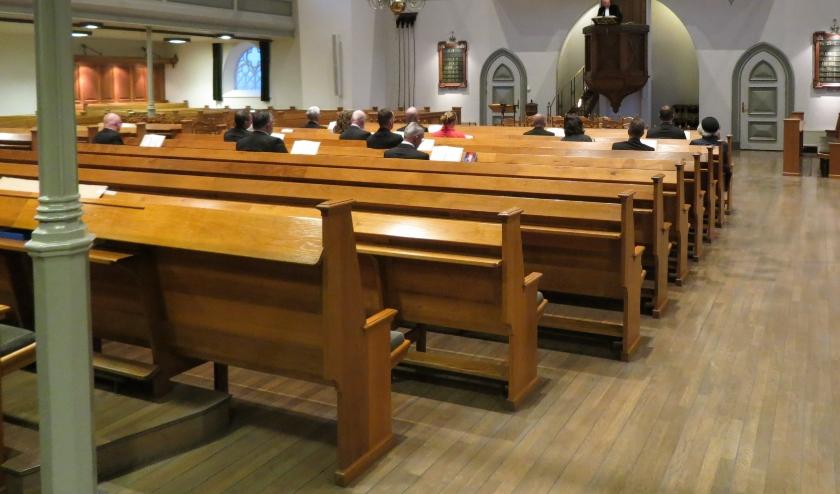• Beeld van de vrijwel lege Grote Kerk. Alleen de ambtsdragers zitten verspreid in de kerk.