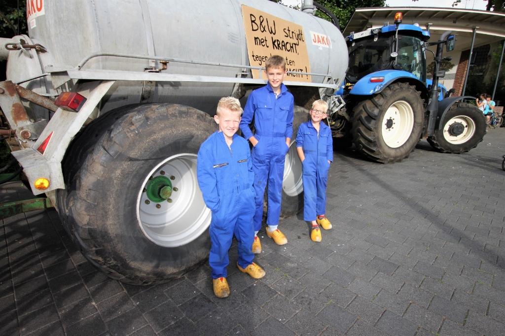 • Drie jongens in overall bij een geparkeerde tractor met mestwagen op Plantsoen de Maenstand in Ouderkerk aan den IJssel.     Foto: Floris Bakker © Krimpenerwaard
