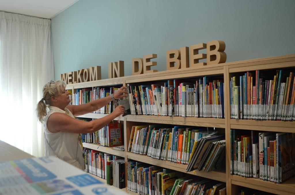 • Thea de Jong geeft de plaatst de gedichten bundels in de bibliotheek. Foto: Aangeleverd © Klaroen