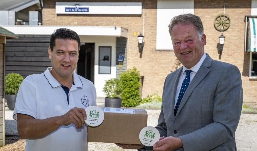 • Anton de Wilde en burgemeester Roel Cazemier met de speciale coronabierviltjes.