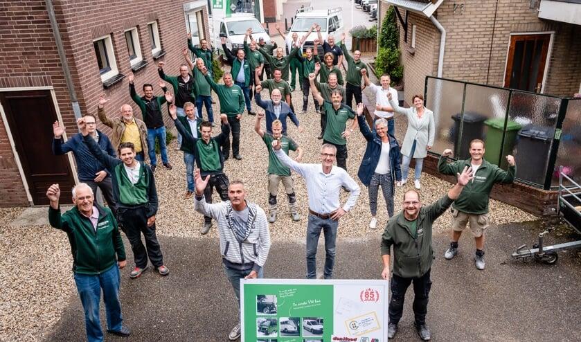 • Het team van Den Hoed Aannemers met het jubileumbord.