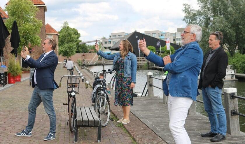 • Rob Smouter en Mirja van Dijk van Leerdamglasstad.nl, Wethouder Cees Taal en raadslid Teus Meijdam staan op de Zuidwal om met de app de Steigerpoort terug te plaatsen op zijn oude plek.