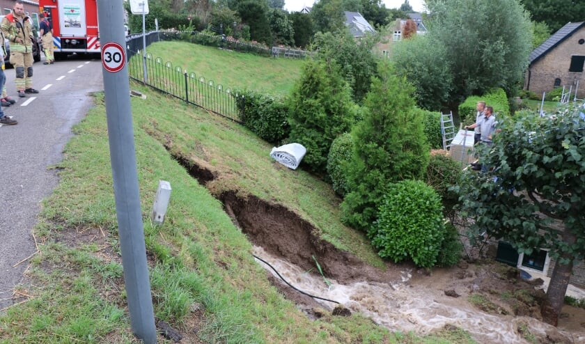 • De schade na de breuk in de waterleiding. Hierdoor ontstond een gat in de dijk onder het wegdek.