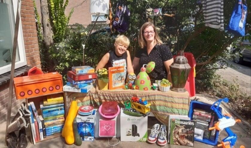 Carola en Koen van Duiven zijn er klaar voor. In hun voortuin maakten ze alvast een leuke rommelmarkt voor de foto. (Foto: Bas van Duiven)