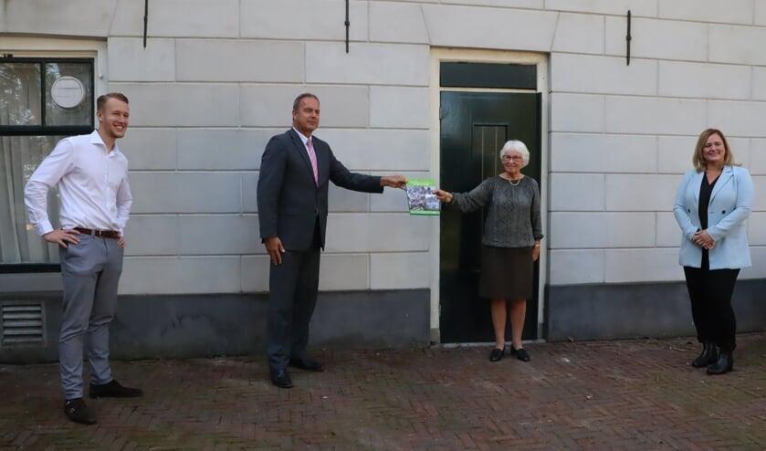 Op de foto overhandigt Barry Ouweneel, een van de vier werkgroepleden die namens de HVWA aan het boek meewerkte, het Plusboek aan burgemeester Paans van Alblasserdam. Monique en Michael van Holten kijken belangstellend toe.