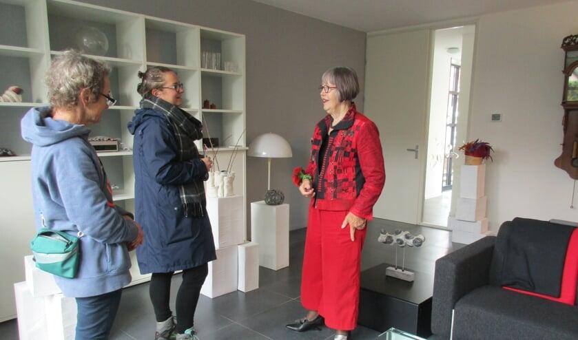 • Margot Odijk in gesprek met twee bezoeksters van haar huiskamerexpositie met vilten objecten.
