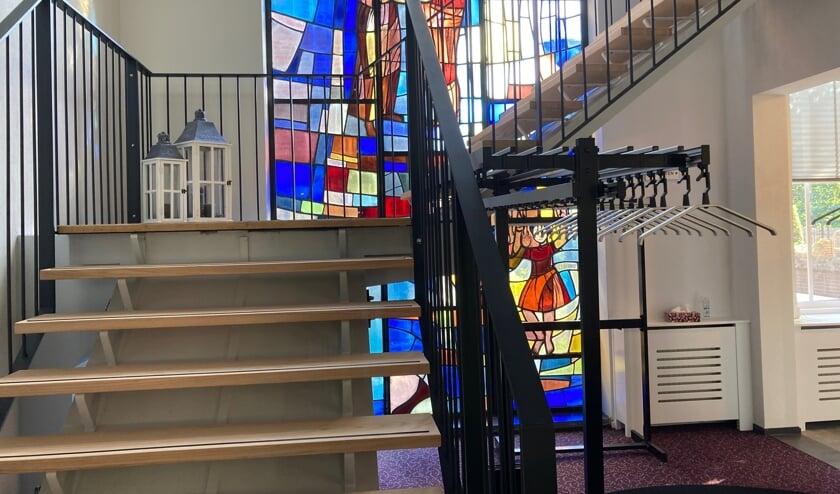 De bredere trap met daarachter het glas-in-loodraam van Nel van der Maaden.