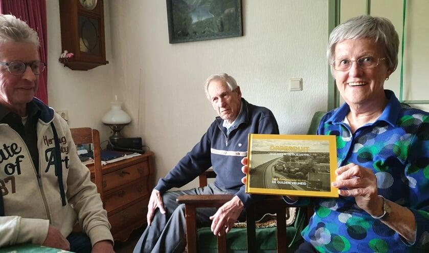 • Janny Manschot neemt het eerste exemplaar van het jubileumboek in ontvangst.