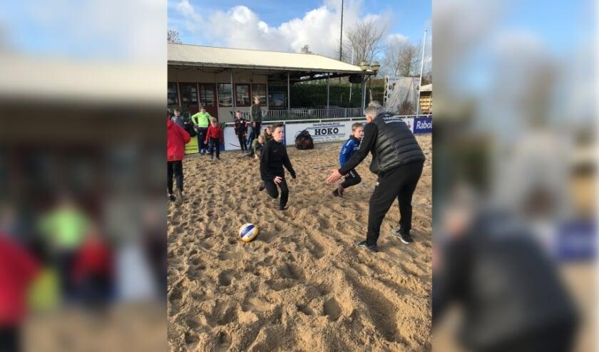 <p>Philip den Haan warmt de jeugd op voorafgaand aan de voetvolleytraining.</p>