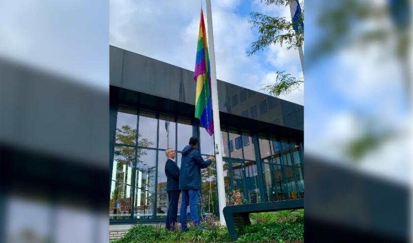 • Wethouder Marc Wilson hijst de regenboogvlag op Coming Out Dag.