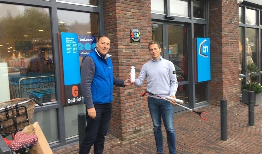 Erik Wiersma ontvangt namens de ondernemers een afvalgrijper van Marco Kortland.