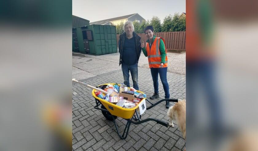 <p>Links Johan de Jong en rechts Anneke Teeuwen. Voor hen de kruiwagen gevuld met voedselwaren.</p>