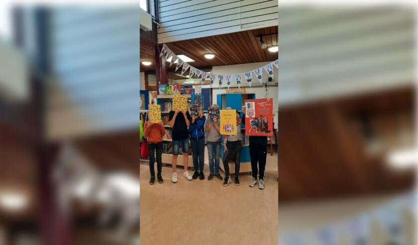 De leerlingenraad van De Bloeiende Betuwe deelt cadeaus, vier prachtige boeken, uit om de Kinderboekenweek feestelijk te starten.