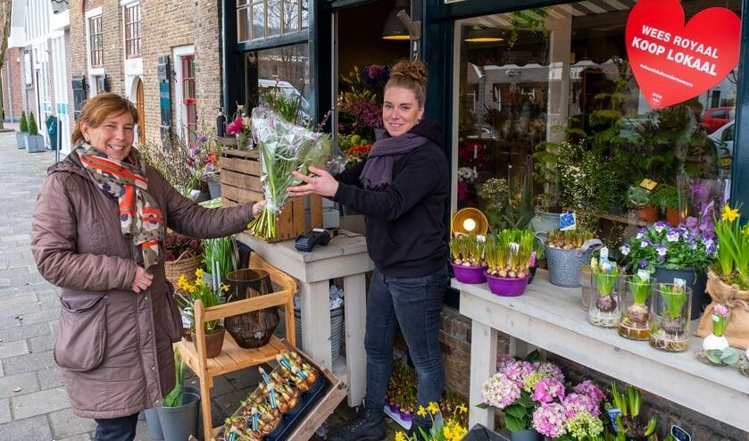 <p>• Michelle van den Berg van Bloembinderij Gewoon Natuurlijk overhandigt een klant een bos bloemen.</p>